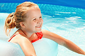 Cute little girl swims in the pool on a rubber ring on a sunny day. Child on summer vacation