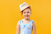 Happy cute beautiful charming little girl in a straw hat and a swimsuit. Closeup portrait of a baby on a yellow background