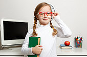 Cute little girl in glasses and a book in her hand. The child stands against the background of the students workplace