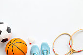 Flat lay of sport balls and rackets on white background. Above view, copy space