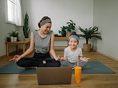 Young mother and daughter making a exercises at home.