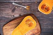 Raw two butternut halves a wood board