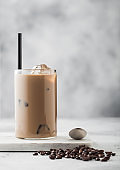 Glass of iced coffee with milk on marble board with spoon and beans on light background