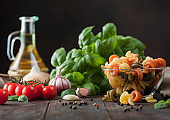 Raw wheat trottole pasta in glass bowl with basil plant, oil and tomatoes with garlic and pepper on wooden background.