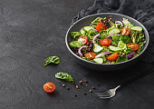 Fresh vegetables salad with lettuce and tomatoes, red onion and spinach in black bowl on dark background with dinner fork