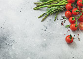 Light food background with asparagus, cherry tomatoes and rosemary on light background