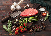 Slice of fresh raw barbeque braising beef steak on chopping board with asparagus and garlic with tomatoes and salt with pepper on wooden background.