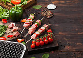 Raw pork kebab with paprika on chopping board with fresh vegetables and disposable charcoal grill on wooden background. Salt and pepper with lettuce and paprika pepper. Top view