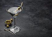 Vodka martini gin cocktail in original glass with olives in metal bowl and bamboo sticks on black.