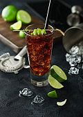 Cuba Libre cocktail in highball glass with ice and lime peel on bamboo stick with straw and fresh limes on black background.