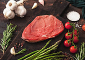 Raw fresh beef braising steak on chopping board with garlic, asparagus and tomatoes with salt and pepper on wooden background.