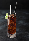 Cuba Libre cocktail in highball glass with ice and lime peel with straw on black background.