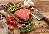Fresh raw barbeque braising beef steak on chopping board with asparagus and garlic with cherry tomatoes and salt with pepper on wooden background.