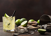 Gimlet Kamikaze cocktail in crystal glass with lime slice and ice on wooden board with fresh limes and strainer with shaker.