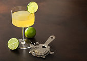 Gimlet Kamikaze cocktail in modern glass with lime slice brown board with fresh limes and strainer.
