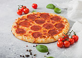 Fresh round baked Pepperoni italian pizza with tomatoes with basil on ligh background with linen towel.