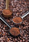 Fresh raw organic ground coffee powder in black, silver and golden steel scoops on top of coffee beans.