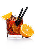 Negroni Cocktail in crystal glass with ice cubes and orange slices with straw and half of fresh orange on white background with reflection with reflection.