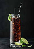 Cuba Libre cocktail in highball glass with ice and lime peel with straw and fresh limes on black background.