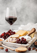 Glass of red wine with selection of various cheese in wooden box and grapes on light table background. Blue Stilton, Red Leicester and Brie Cheese with Cheddar and nuts with honey.