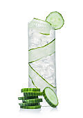 Fresh cold cucumber water in highball glass with ice cubes and cucumber slices on white. Healthy and refreshing organic drink.