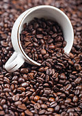 White ceramic cup with coffee beans inside fresh aroma roasted coffee beans background.