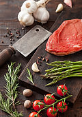 Beef braising steak, fresh raw slice on chopping board with garlic, asparagus and tomatoes with salt and pepper on wooden background.