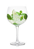 Glass of Mojito summer alcoholic cocktail with ice cubes mint and lime on white.