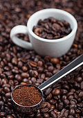Fresh raw organic ground coffee powder in black steel scoop with white epresso cup on top of coffee beans.