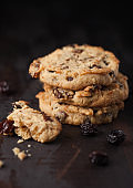 Homemade organic oatmeal cookies with raisins and apricots on dark wooden background.