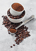 Fresh raw organic coffee beans in white bowl and powder on ligh background with round steel scoop.