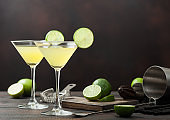 Gimlet Kamikaze cocktail in martini glasses with lime slice and ice on wooden board with fresh limes and strainer with shaker.
