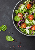 Fresh healthy vegetarian vegetables salad with tomatoes and cucumber, red onion and spinach in large grey bowl plate on dark background.