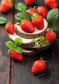 Fresh raw organic strawberries with leaf on timber plate on wooden background.