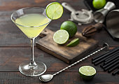 Gimlet Kamikaze cocktail in martini glass with lime slice and ice on wooden board with fresh limes and strainer with shaker.