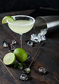 Glass of Margarita cocktail with fresh limes and bar spoon with ice cubes in shaker on wooden background.
