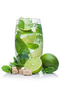 Glass of Mojito summer alcoholic cocktail with ice cubes mint and lime on white with cane sugar and raw lime