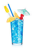 Blue lagoon cocktail highball glass with straw,stirrer and orange slice with sweet cherry and umbrella on white. Vodka and blue curacao liqueur mix.