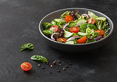 Cucumbers and tomatoes, red onion and spinach mix in fresh vegetables salad in grey bowl plate on dark background.
