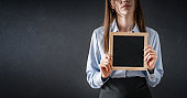 Business woman holding chalkboard in hand
