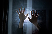creepy horror scene, person's hands in the dark behind the glass, abstract shadow fear