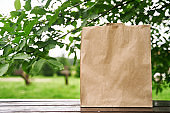 Blank paper bag stands on a wooden table against the background of green leaves. Shopping concept. Copy space