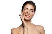 Smiling naked girl applying scrub on face skin