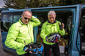 Two Senior Men Removing Their Cycling Helmet After Bicycle Trip - stock photo