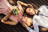 Bride and Bridegroom Lying Down Outdoors and Relaxing Together