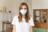 Portrait of pretty 30s young millennial woman with facial medical mask, virus outbreak protection, healthcare concept