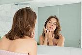 Girl looking at mirror examining skin