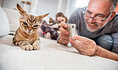Proud Mature Man Taking Photos of his Relaxed Devon Rex Cat with Smart Phone - stock photo