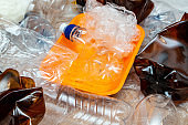 Lot of used plastic, crumpled empty bottles, packets, plastic orange dish, diaper, pollution recycle eco concept background close up selective focus