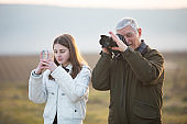 Grandfather Photographing With a Camera While Granddaughter is Photographing With Smart Phone